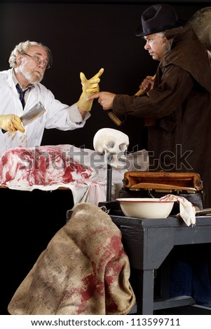 Evil doctor interacts with grave robber over bloody corpse. Stage effect, isolated on black background, spot lighting. - stock photo