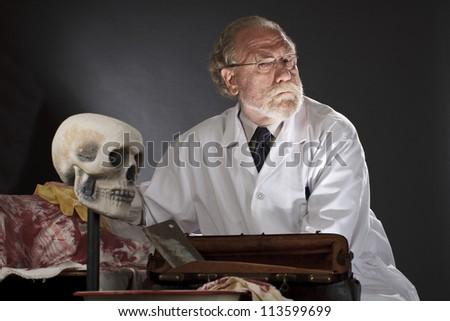 Evil doctor with surgical tools and bloody corpse. Sinister expression, dark background with dramatic low angle spot lighting. Horizontal, copy space. - stock photo