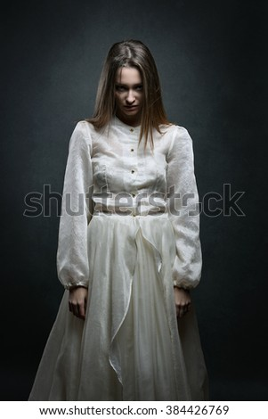 Evil expression on beautiful pale woman. Dark portrait