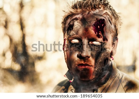 Evil face of a charcoal black zombie standing in smouldering horror forest with blank gaze. Undead boy sets fire. - stock photo