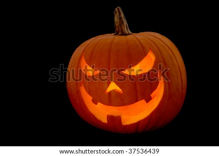 Evil-faced glowing Halloween pumpkin, isolated on black - stock photo