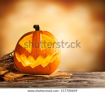 Evil halloween pumpkin on wood with free space for text - stock photo