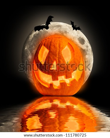 Evil halloween pumpkin with bats silhouettes, reflected in water surface - stock photo