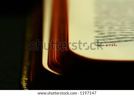 Evil hightlighted on a bible. - stock photo