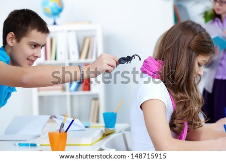 Evil lad holding black spider while going to frighten his classmate at lesson - stock photo