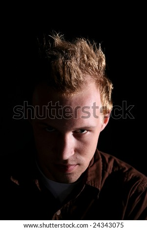 evil looking man with half of his face in the shadows - stock photo
