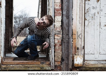 Evil looking possessed man in destroyed building - stock photo