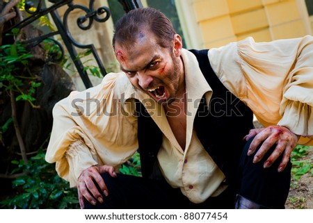 Evil male vampire with wounded face, roaring scary at camera