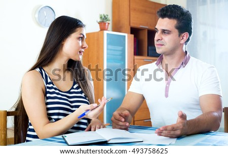 Evil man and woman sitting at home with notes