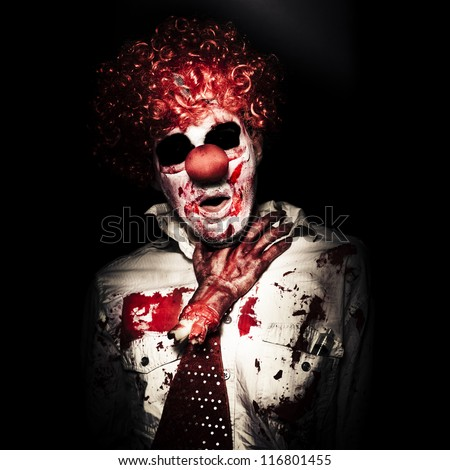 Evil Portrait Of A Creepy Clown Getting Chocked By A Dead Amputated Hand On Dark Studio Background - stock photo