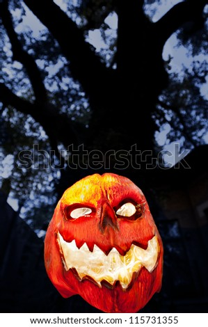 Evil Pumpkin - Jack O Lantern with Dark Tree and Houses - stock photo