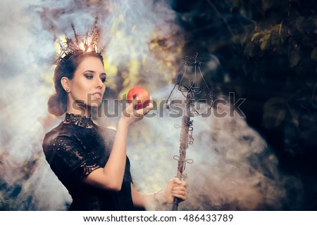 Evil Queen with Poisoned  Apple in Misty Decor - Beautiful dark princess using black magic spell