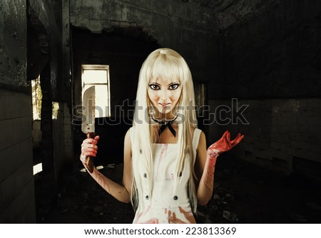 Evil smiling woman in the style of doll  killer, zombie or a ghost with a bloody hatchet in hand - stock photo