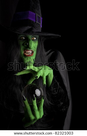 Evil witch and her crystal ball, black background. - stock photo