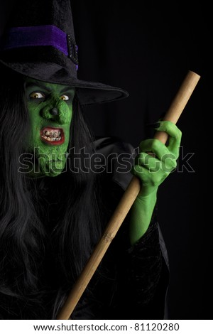Evil witch flying on her broom stick, black background - stock photo