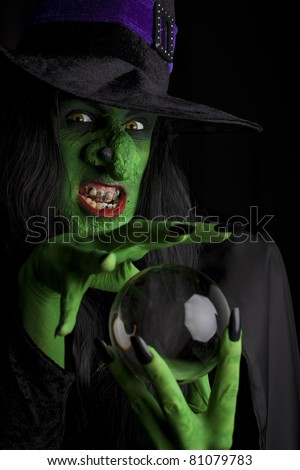 Evil witch looking into her crystal ball, black background. - stock photo