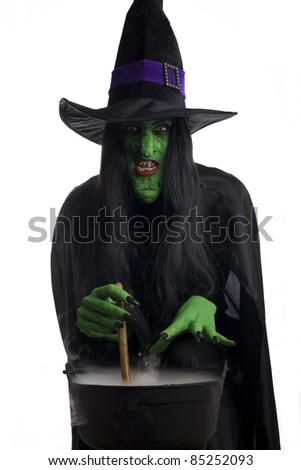 Evil witch stirring her misty cauldron, white background. - stock photo
