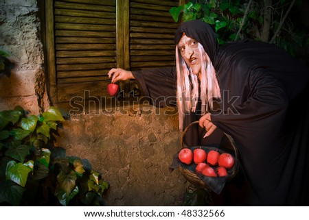 Evil witch with poisoned apple outside a house