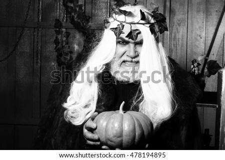 Evil wizard with long hair and beard in wreath of ivy with pumpkin in old wooden house, black and white