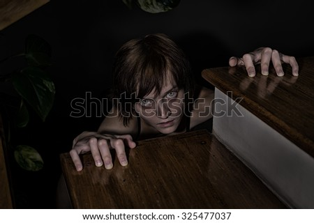 Evil zombie girl crawling to you from under the stairs