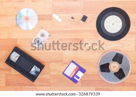 Evolution of information carrier from analog to digital. Objects on wooden background. - stock photo