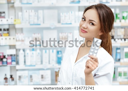 Exactly what you need. Portrait of an adorable professional pharmacist holding pills looking to the camera smiling. - stock photo