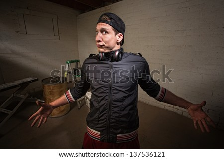 Exaggerating young man with arms wide open - stock photo