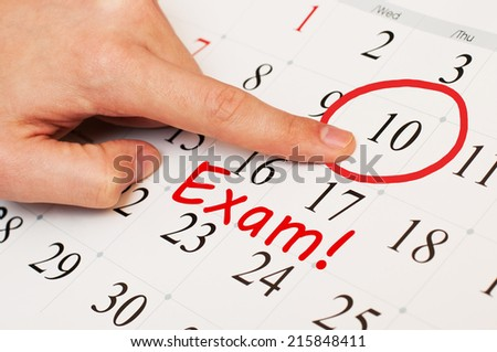 Exam date is circled on a calendar page with a red marker - stock photo