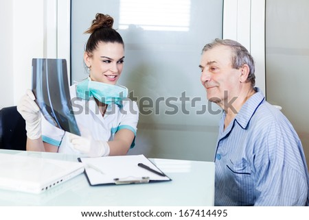Exam room: Female doctor and patient looking X-ray - stock photo