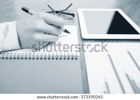 Examination paper on the office desk. Hand marks the estimate. Toning in cold tones. - stock photo