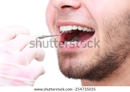 Examine of young man by dentist isolated on white background
