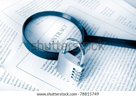 examining a contract with padlock to represent security and confidentiality - stock photo