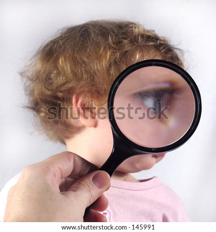 Examining baby with magnifying glass - stock photo
