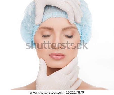 Examining face before plastic surgery. Portrait of beautiful young woman in medical headwear keeping eyes closed while hands in gloves examining her face isolated on white - stock photo
