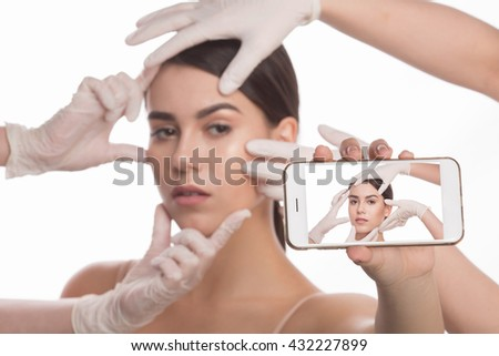 Examining face concept. Closeup portrait of mobile phone with screen in front of beautiful lady during examination of her face by cosmetologists. - stock photo