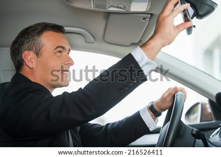 Examining his new car. Side view of cheerful mature man in formalwear adjusting mirror while sitting in his car - stock photo