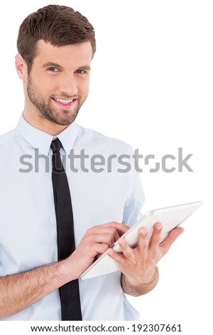 Examining his new gadget. Cheerful young man in formal wear working on digital tablet and smiling while standing isolated on white background - stock photo