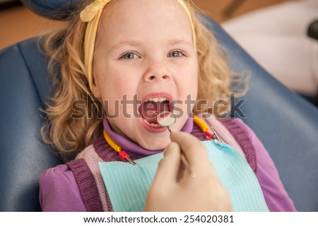 Examining teeth of small patient at dentist. Close-up of small female patient at dentist's  - stock photo