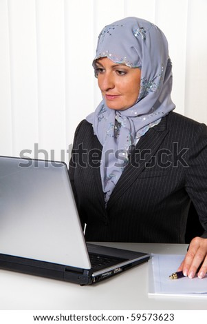 Example picture Islam. Muslim, Woman with headscarf in an office - stock photo