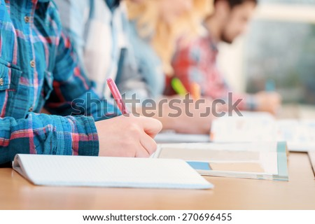 Exams. Cropped view of students writing a test in their exercise books - stock photo