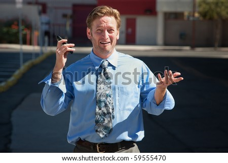 Exasperated business man with cell phone outdoors - stock photo