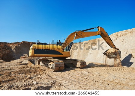 exavation machine excavator at earthmoving work in sand quarry - stock photo