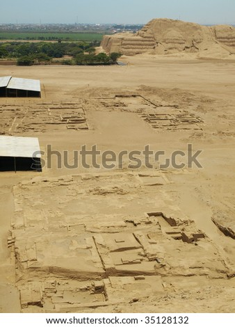 Excavated dwellings on desert floor with the largest single prehistoric structure in Peru in background, Huaca del Sol. Built by the ancient Moche culture. - stock photo
