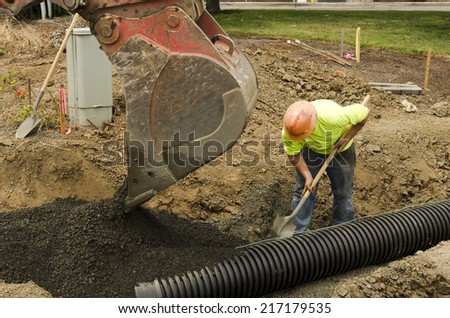Excavation construction contractor installing a domestic black plastic sewer drain on a new commercial street filling with gravel - stock photo
