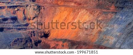 excavator against iron-ore pit - stock photo