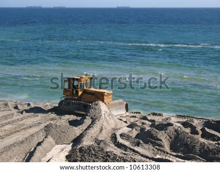 Excavator and bulldozer being used to construct sea defenses on the beach - stock photo