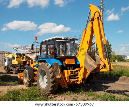 Excavator and crane on background of blue sky with clouds - stock photo