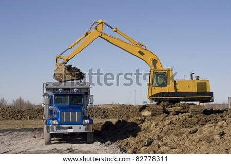 Excavator and dumptruck on construction site - stock photo