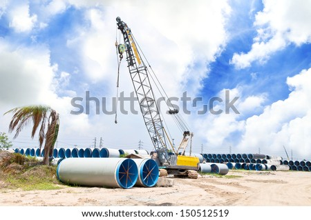 Excavator and numerous water pipes - stock photo