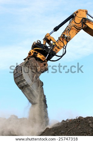excavator arm and bucket scoop full of dirt at construction site - stock photo